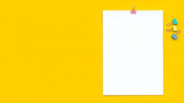 Livre blanc avec un trombone sur fond jaune.