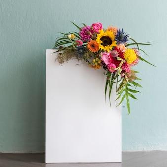 Livre blanc vierge avec un bouquet de fleurs colorées