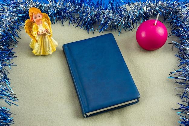 Livre bleu sur un plaid et fond de noël.