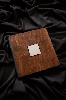 Livre en bois avec plaque signalétique sur fond de tissu noir.