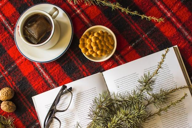 Livre et brindilles de conifères près du thé et des biscuits
