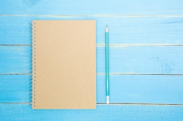 Livre brun et un crayon sur le vieux fond en bois bleu - vue de dessus