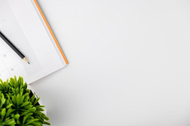 Livre de calendrier et pencle et petit arbre blanc isolé, travail de l'entreprise, fond de vue de dessus concept