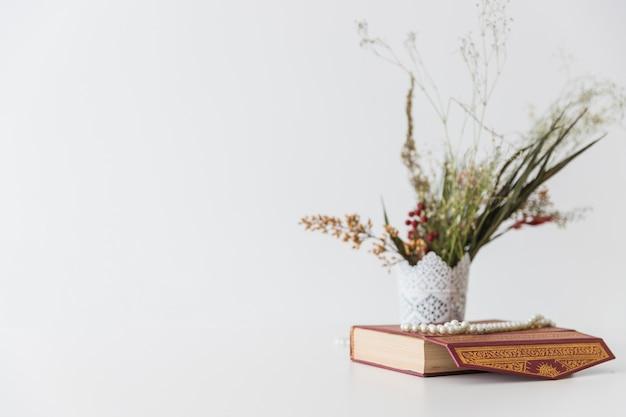 Livre de coran et fleurs dans un vase