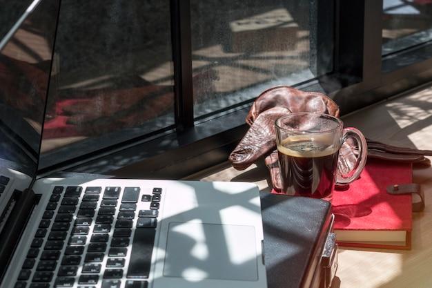 Livre de correspondance, ordinateur portable, gants de cuir marron et café noir sur bois.