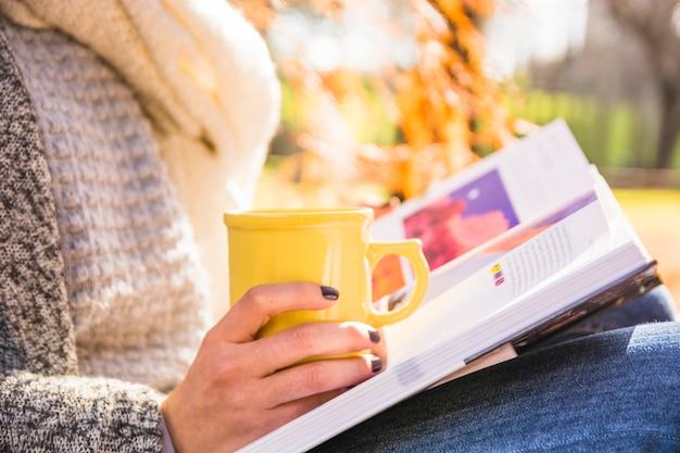 Livre et coupe sur les genoux en automne parc