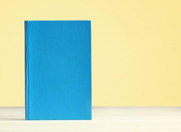 Livre avec une couverture blanche bleue sur la table sur un fond jaune.