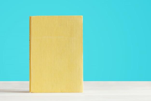 Livre avec couverture jaune vierge sur une table en bois.