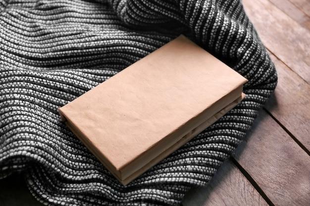Un livre et une couverture de laine sur le sol
