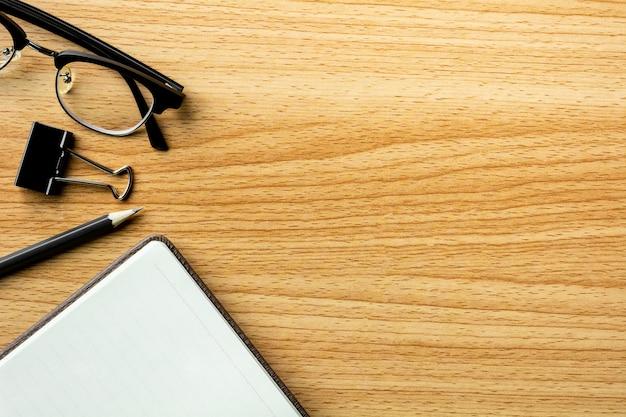 Livre, crayon et lunettes sur un bureau en bois. - pour fond de concept créatif et commercial.