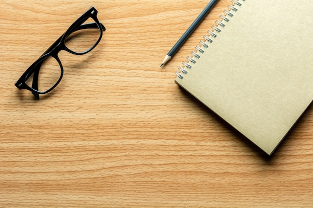 Livre, crayon et lunettes sur un bureau en bois