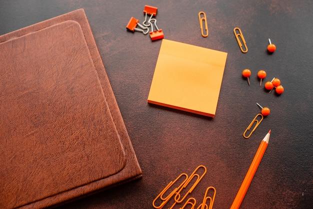 Le livre, le crayon, les trombones et les feuilles de marques se trouvent sur un bureau