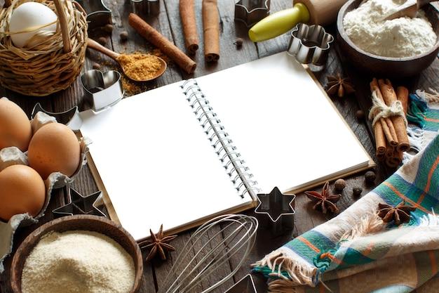 Livre de cuisine vierge, ingrédients et ustensiles vue de dessus