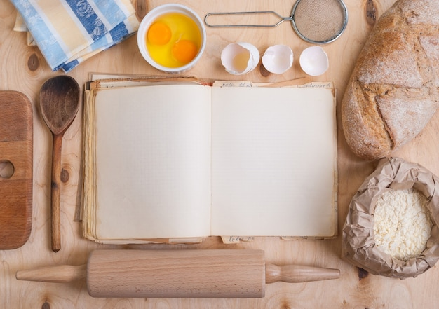 Livre de cuisine vierge, planche à découper, coquille d'oeuf, pain, farine, rouleau à pâtisserie. table en bois vintage d'en haut.