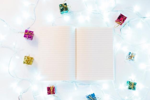 Livre d'écriture entre cadeaux et guirlandes