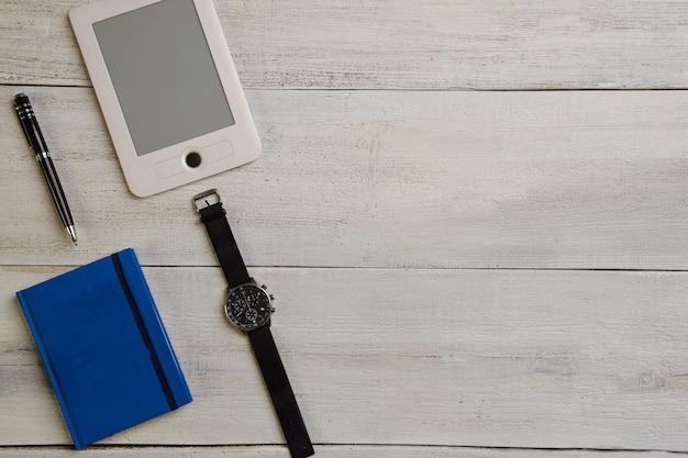 Un livre électronique, une montre-bracelet, un agenda et un stylo se trouvent sur une table en bois beige.