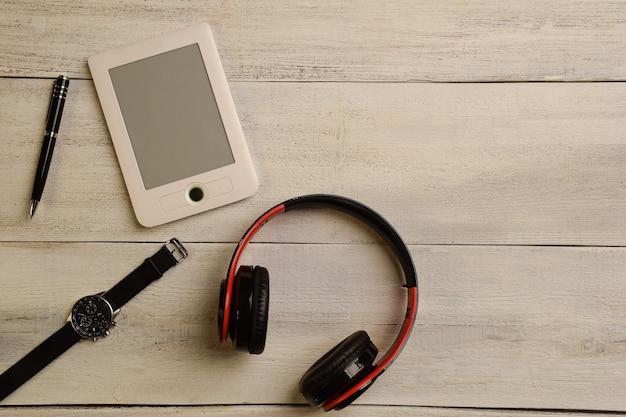Un livre électronique, une montre-bracelet, des écouteurs et un stylo se trouvent sur une table en bois beige.