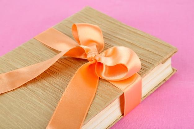 Livre enveloppé d'un ruban de couleur
