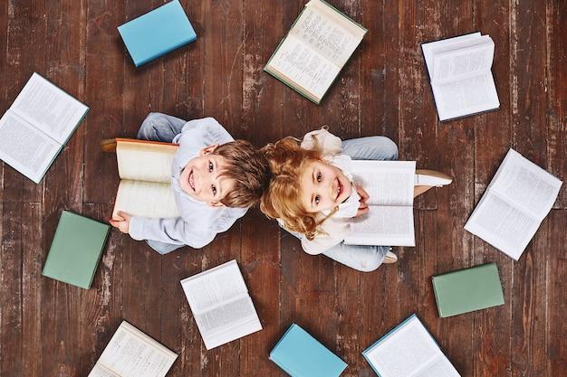 Un livre est comme un jardin transporté dans la poche des enfants assis près des livres tout en