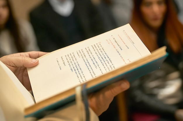 Livre de l'evangile tenu par le prêtre lors d'une célébration catholique dans une église pleine de fidèles.