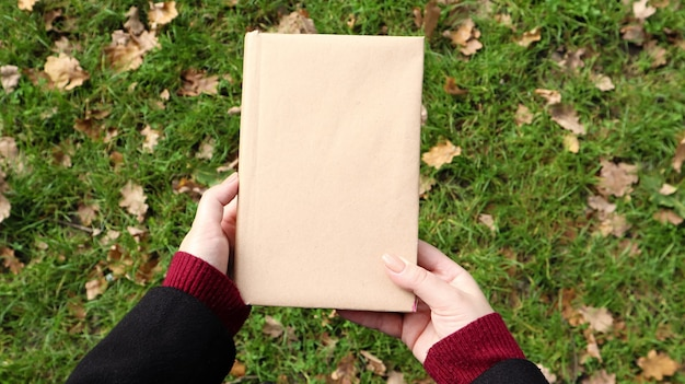 Un livre fermé dans une couverture en papier kraft dans des mains féminines avec de l'herbe verte et des feuilles jaunes tombées en arrière-plan. mise à plat, vue de dessus. modèle, mise en page. espace de copie.
