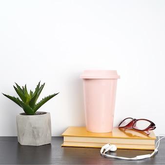 Livre fermé et verre en céramique rose avec café sur une table noire