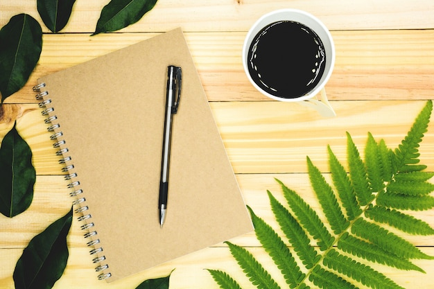 Un livre avec des feuilles vertes sur une table en bois