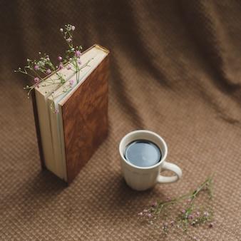 Un livre avec des fleurs et une tasse de café