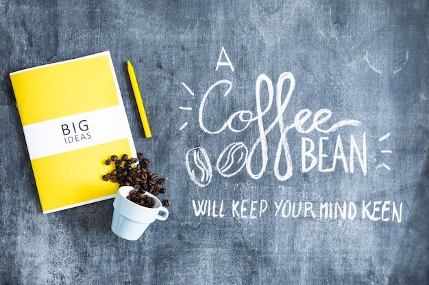 Livre de grandes idées avec des grains de café renversés de la tasse et du texte sur le tableau noir