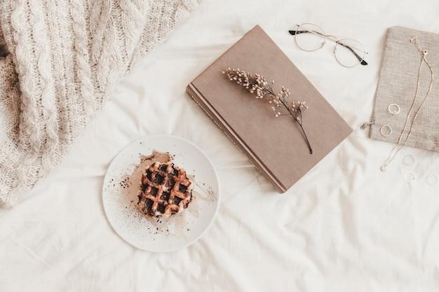 Livre avec herbe près de pain sur plaque et autres choses sur drap de lit