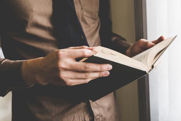 Livre de holding homme d'affaires à la fenêtre. idée de création d'entreprise créative.