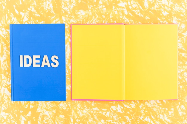 Livre d'idées près du livre jaune ouvert sur fond jaune
