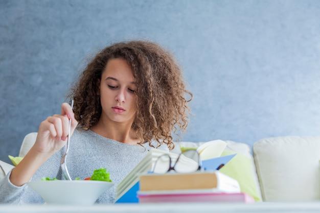 Livre de lecture adolescente cheveux bouclés et salade