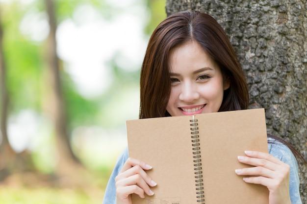 Livre de lecture belle femme asiatique dans le parc en vacances auto-apprentissage