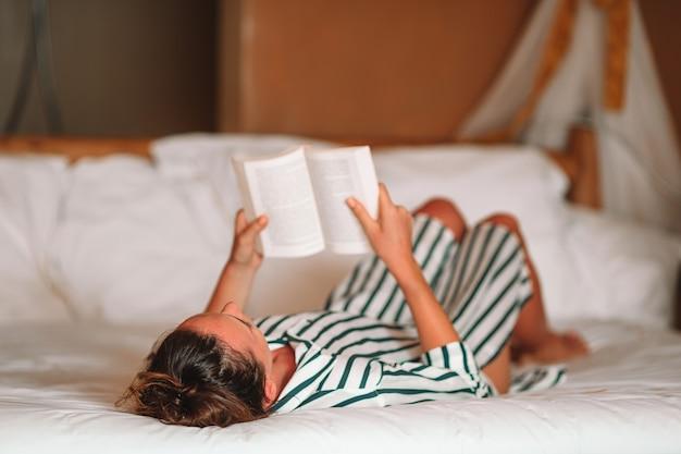 Livre de lecture de belle femme au lit se détendre