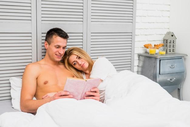 Livre de lecture de couple au lit
