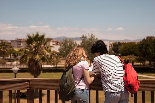 Livre de lecture de couple près d'une clôture en bois au fond de la ville