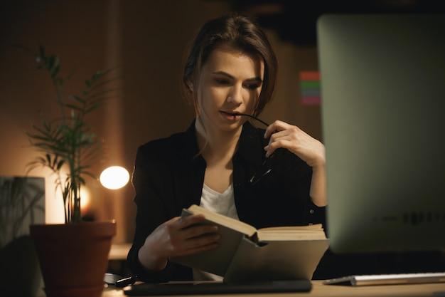 Livre de lecture de designer sérieux jeune femme. en regardant de côté.