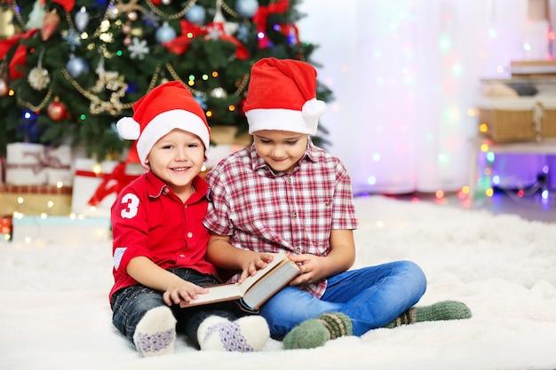 Livre de lecture de deux petits frères mignons sur la surface de décoration de noël