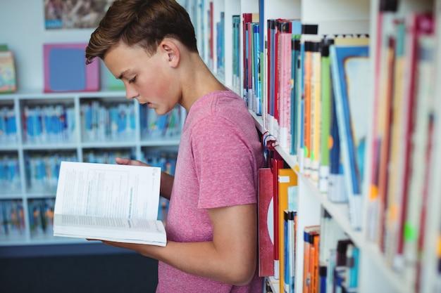 Livre de lecture d'écolier attentif dans la bibliothèque
