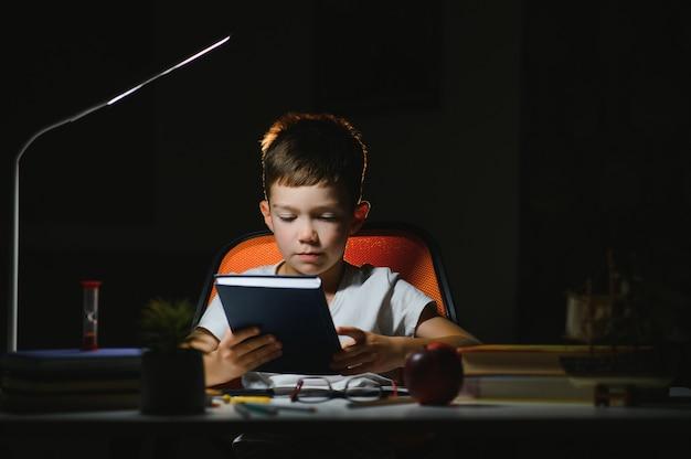 Livre de lecture d'écolier concentré à table avec livres, plante, lampe, crayons de couleur, pomme et manuel