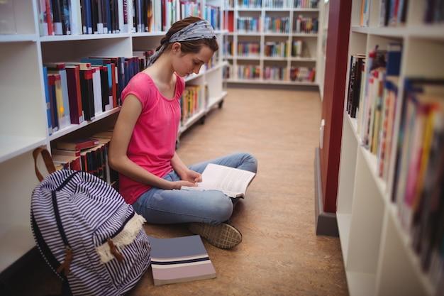 Livre de lecture d'écolière attentif dans la bibliothèque