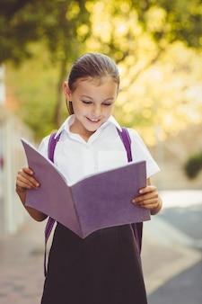 Livre de lecture d'écolière heureux sur le campus