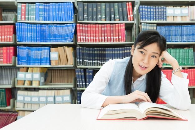 Livre de lecture d'un étudiant asiatique dans une bibliothèque