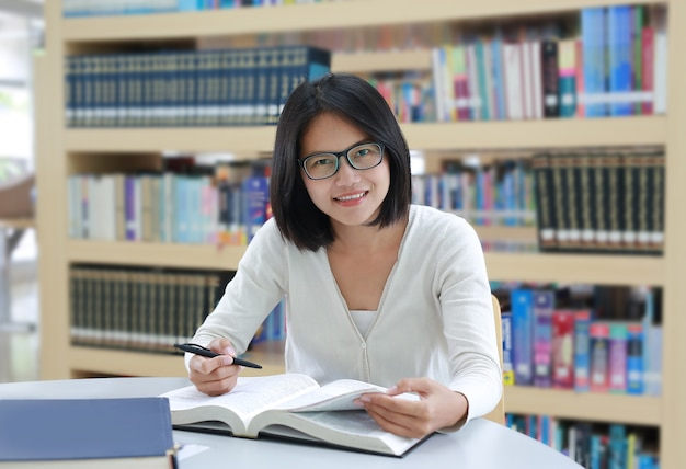 Livre de lecture d'un étudiant asiatique avec sourire et regardant directement dans la bibliothèque