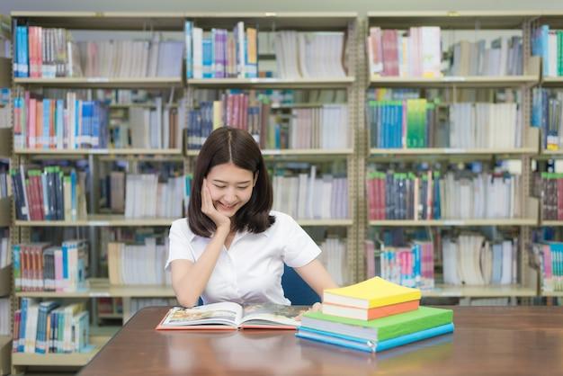Livre de lecture d'étudiant en bibliothèque à l'université.