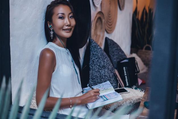 Livre de lecture de femme au café, portrait en plein air, asiat