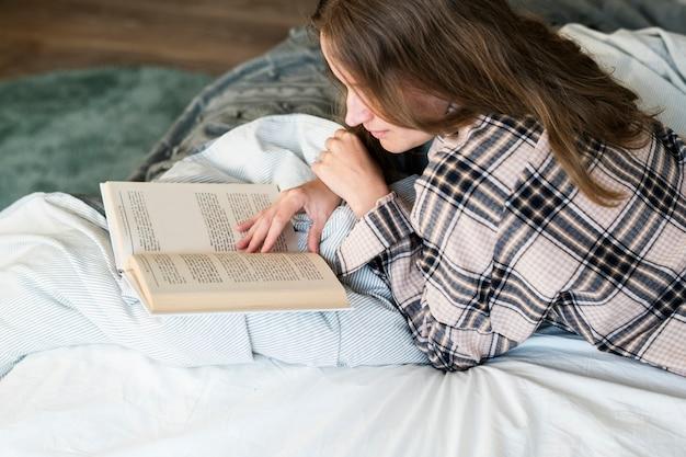 Livre de lecture de femme caucasien au lit