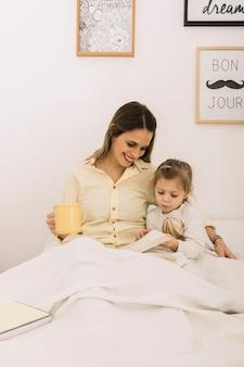 Livre de lecture de femme joyeuse avec sa fille dans la matinée
