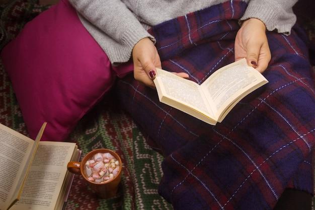 Livre de lecture de femme sous couverture avec tasse de boisson chaude